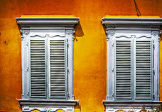 Windows in an orange wall in Florence Royalty Free Stock Images