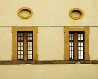 Windows and Oval Frames on a Wall in Italy Royalty Free Stock Photography