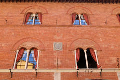 Windows in a red brick wall in Pisa Stock Photography