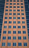 Windows of a red building. Windows of a terracotta-colored modern high-rise building stock images