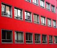 Windows on red facade Stock Images