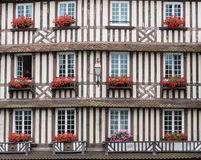 Windows with red flowers. Brown windows with pink,red flowers in France stock photos