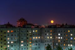 Windows, roofs and facade of an mass apartment buildings in Russia at full moon night. Telephoto closeup shot stock photos