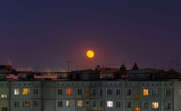 Windows, roofs and facade of an mass apartment buildings in Russia at full moon night. Telephoto closeup shot royalty free stock photography