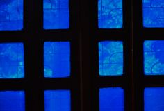 Windows of a room the light is playing through the blue glass of the window royalty free stock photos