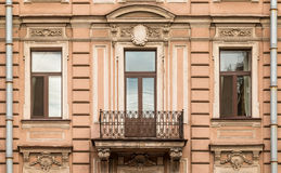 Windows in a row and balcony on facade of apartment building. Three windows in a row nd balcony on facade of urban apartment building front view, St. Petersburg Royalty Free Stock Images