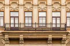 Windows in a row and balcony on facade of office building. Several windows in a row and balcony on facade of urban office building front view, St. Petersburg Royalty Free Stock Image