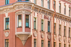 Windows in a row and bay window on facade of apartment building. Many windows in row and bay window on corner of facade of urban apartment building angle view Stock Photos