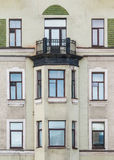 Windows in a row and bay window on facade of apartment building Stock Images