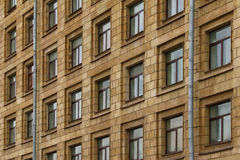 Windows in a row on facade of apartment building. Many windows in row on facade of urban apartment building in St. Petersburg, Russia Stock Photo