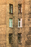 Windows in a row on facade of apartment building. Several windows in row on facade of urban apartment building angle view, St. Petersburg, Russia Royalty Free Stock Photo