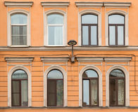 Windows in a row and streetlight on facade apartment building Royalty Free Stock Images
