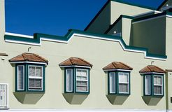Windows and shingles. Building exterior wall with four windows and wooden shingles stock photography