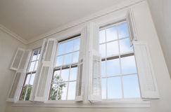 Windows and shutters. Sky seen through windows with louver shutters Stock Photo