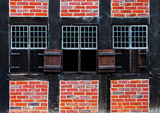 Windows with shutters in brick wall of the half timbered house Royalty Free Stock Image