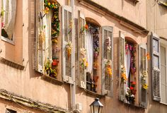 Fake flowers - Grasse. Windows and shutters decorated with colorful fake flowers - Grasse, France Stock Photos