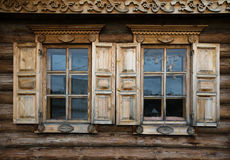 Windows with shutters, patterned on the wall of the old wooden h Royalty Free Stock Photos