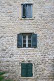 Windows with shutters in the three storey building Stock Photo