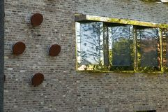 Windows with strong reflecting frames. Bricks facade of a modern office building with windows with golden reflecting frames Royalty Free Stock Photos