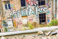 Windows su una costruzione rovinata con i graffiti Immagine Stock