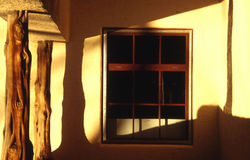 Windows at sunset. Window with square panes under the golden light of the sunset. Mexican-styled architecture Stock Photos