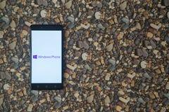 Windows-Telefonlogo auf Smartphone auf Hintergrund von kleinen Steinen Lizenzfreies Stockbild