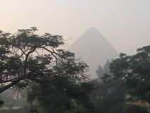 Giza great pyramid tomb Cairo Egypt. Great pyramid Giza Egypt Egyptian tomb stones trees misty ancient Cheops pharaoh seven wonders vacation tourism necropolis Stock Photos