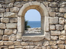 Windows to the sea. The window of an ancient building with view of the sea Stock Photo