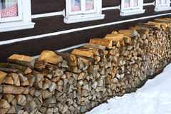 Windows of a traditional country cottage house with firewood logs Royalty Free Stock Photo