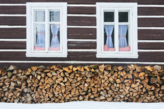 Windows of a traditional country cottage house with firewood logs Stock Photo