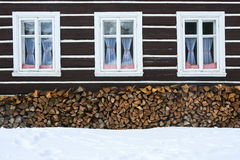 Windows of a traditional country cottage house with firewood logs Stock Photos