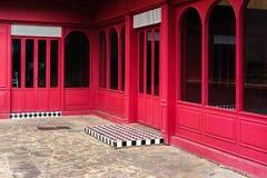 Windows und Türen auf hellem rotem Gebäude Stockfotos