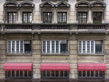 Windows w starym betonowym budynku w centrum miasto z czerwoną markizą zdjęcie royalty free