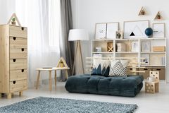 Windows with drapes. Windows with white and grey drapes in bright teenager room interior with futon mattress couch, wooden rack and minimal posters stock photos