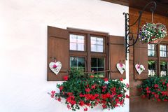 The windows of the wooden house are beautifully decorated with white hearts and flowers stock images