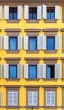 Windows on yellow facade Stock Photos