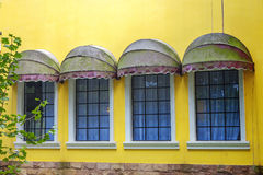 Windows on yellow wall Stock Photos