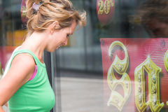 Windowshopping. Pretty blond girl window shopping Royalty Free Stock Photography