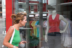Windowshopping. Pretty blond girl checking out the window display of a clothing store Stock Images