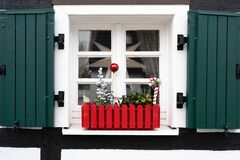 Window sill with Christmas decoration in red flower box. Small Christmas tree, red ball and red and white candy cane.