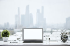 Windowsill with white laptop. Closeup of blank white laptop on windowsill with a glass of water, alarm clock, glasses, decorative plant and other items on blurry stock photo