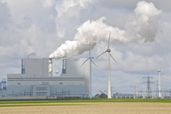 Windpowered generators next to a large Fossil-fuel Power Plant Stock Photo