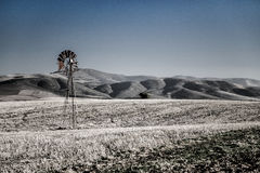 Windpump and hills. A slightly desaturated landscape image of a windpump with hills in the background Stock Photos