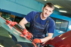Windscreen repairman. Portrait of automobile glazier repairman at windscreen or windshield of a car replacement in auto service station garage Stock Photo