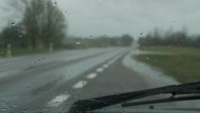 Windscreen wipers cleaning windshield glass on rainy day. stock video footage