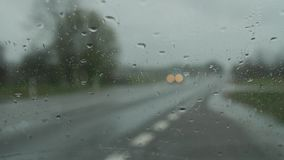 Windscreen wipers cleaning windshield glass on rainy day. stock footage