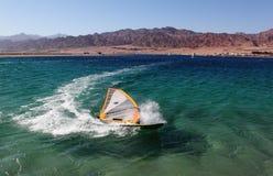 Windserf tombant dans l'eau sur le virage pointu Image libre de droits