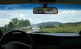 Windshield. Line of cars, ride in a car, view outside in front of car, automobile was going in front of us next car, rearview mirror view, outside view of Royalty Free Stock Photo