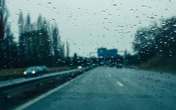 Windshield full with water drops on a heavy rain on highawy. Water drops on wwindshield - Personal perspective of driver inside car looking at the front view of royalty free stock photography