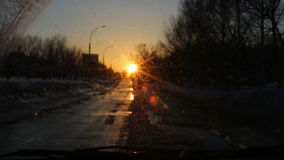 Windshield view of sunset at the city road, beautiful lens flare stock video footage